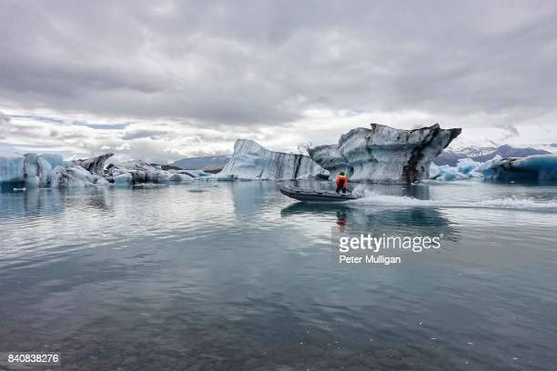 A rigid inflatable boat skims over the glacier lake at Jokulsarlon, Iceland