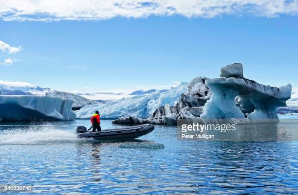 rigid inflatable boat speeding across glacier lagoon, jökulsárlón, iceland - glacier lagoon stock photos and pictures