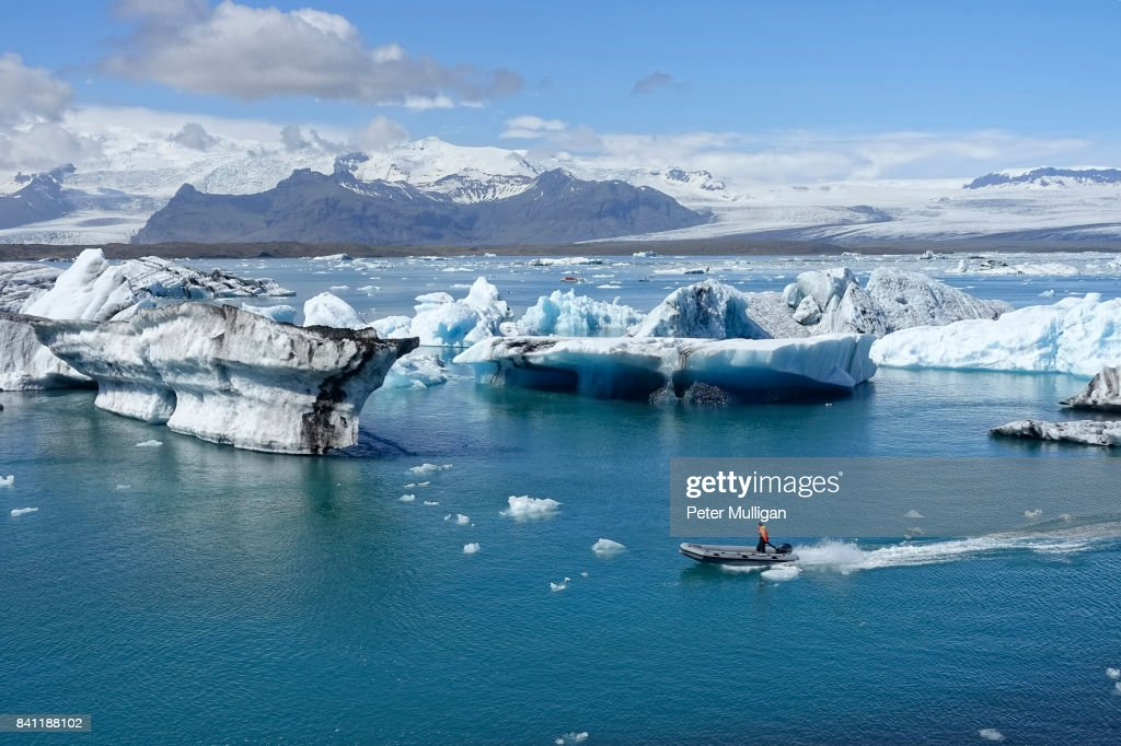 A rigid inflatable boat threads its way through icebergs in the glacier lagoon at Jokulsarlon, Iceland : Stock Photo