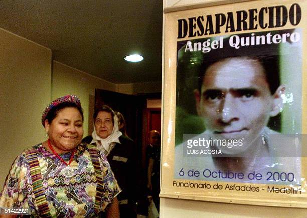 Rigoberta Menchu 1992 Nobel Prize for Peace winner and Marta de Vasquez president of the Mothers of Plaza de Mayo pass in front of a poster of a...