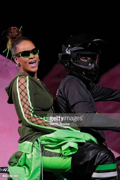 Rihanna greets the audience on the back of a motorcycle after the conclusion of her Fenty Puma By Rihanna Runway show in September 2017 New York...