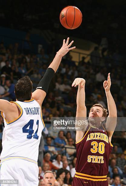 Rihards Kuksiks of the Arizona State Sun Devils puts up a shot over Nikola Dragovic of the UCLA Bruins during the college basketball game at Pauley...