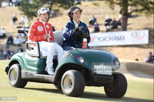 Riho Fujisaki of Japan sits in golf cart as she is driven to the 18th tee for a playoff during the final round of the Yokohama Tire PRGR Ladies Cup...