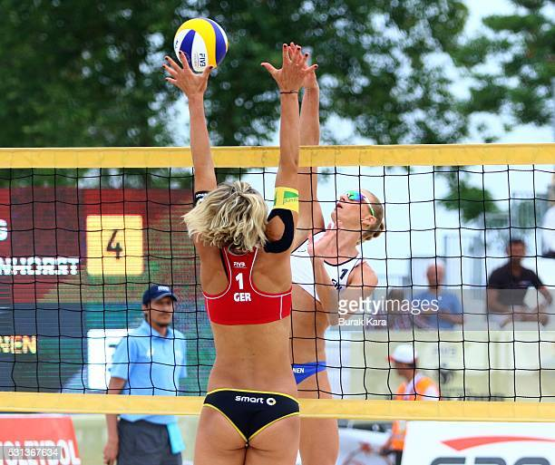 Riikka Lehtonen of Finland jumps to spike the Mikasa past a blocking Kira Walkenhorst during the women's final match of the FIVB Antalya Open beach...
