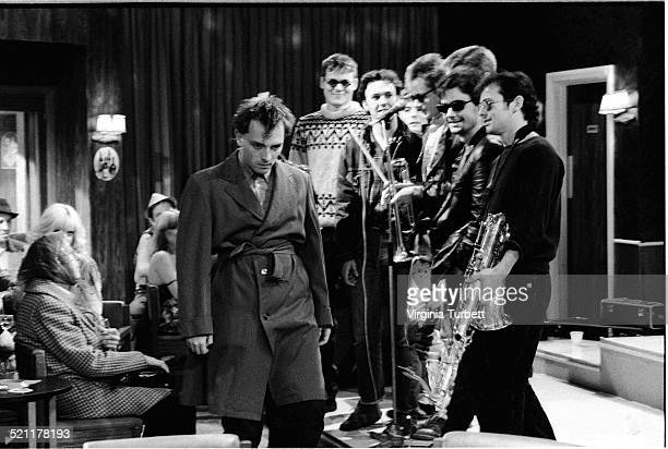 Rik Mayall as Rick stands in front of the members of the band Madness on set during the filming of The Young Ones episode 'Boring' UK 19 August 1982
