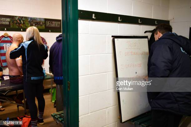 Rik Orkney Head Coach of OPMs writes on a whiteboard in the changing room prior to the Lockie Cup Semi Final match between Old Plymouthian and...