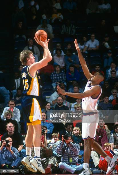 Rik Smits of the Indian Pacers shoots over Juwan Howard of the Washington Bullets during an NBA basketball game circa 1995 at US Airways Arena in...