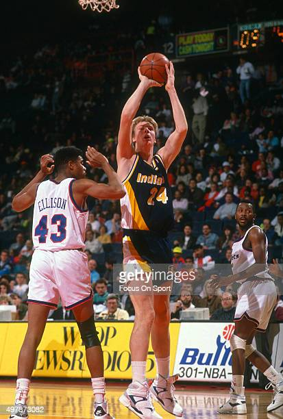 Rik Smits of the Indian Pacers shoots over Pervis Ellison of the Washington Bullets during an NBA basketball game circa 1990 at the Capital Centre in...