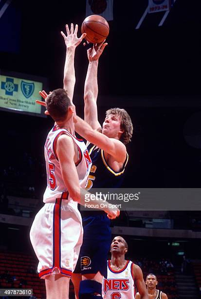 Rik Smits of the Indian Pacers shoots over Shawn Bradley of the New Jersey Nets during an NBA basketball game circa 1997 at Continental Airlines...