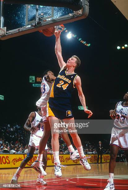 Rik Smits of the Indian Pacers slam dunks the ball over Pervis Ellison of the Washington Bullets during an NBA basketball game circa 1992 at the...