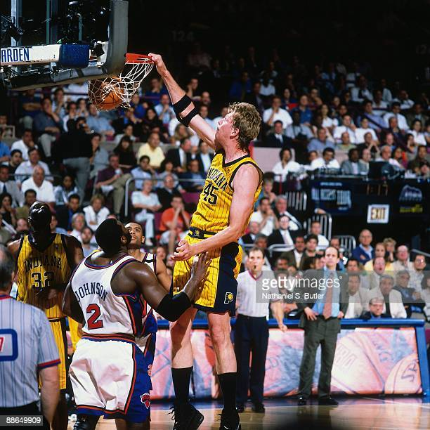 Rik Smits of the Indiana Pacers dunks against Larry Johnson of the New York Knicks in Game Four of the Eastern Conference Finals during the 1999 NBA...