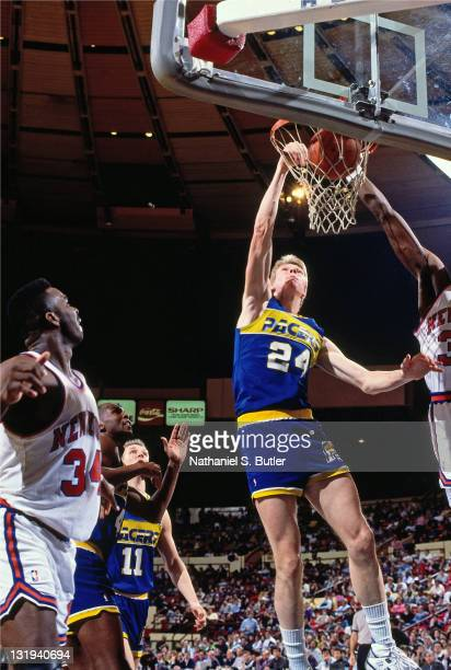 Rik Smits of the Indiana Pacers dunks against Patrick Ewing of the New York Knicks circa 1989 at Madison Square Garden in New York City NOTE TO USER...