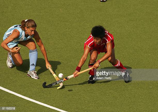 Rika Komazawa of Japan and Marine Russo of Argentina fight for the ball in the women's field hockey preliminaries on August 16 2004 during the Athens...
