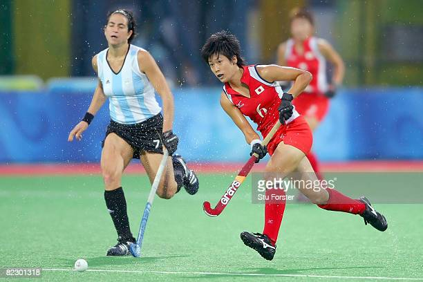 Rika Komazawa of Japan move against the defense of Mariana Gonzalez Oliva of Argentina during the women's pool hockey match at the Olympic Green...