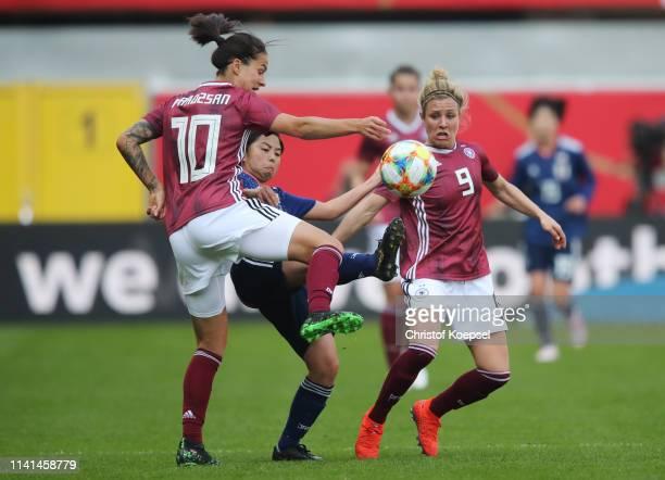 Rikako Kobayashi of Japan battles with Dzsenifer Marozsan and Svenja Huth of Germany during the Women's International Friendly between Germany and...