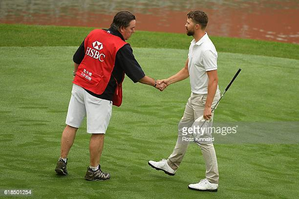 Rikard Karlberg of Sweden shake hands with caddie Mick Donaghy on the 18th green during day one of the WGC HSBC Champions at Sheshan International...
