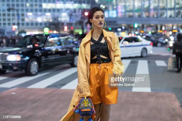 Rikarin is seen wearing tan boots orange nylon shorts black banded top yellow coat monster bag during the Amazon Fashion Week TOKYO 2019 A/W on March...