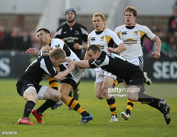 Riki Flutey of Wasps is tackled by Alex Tait and Hall Charlton during the Guinness Premiership match between Newcastle Falcons and London Wasps at...