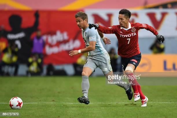 Riki Matsuda of Avispa Fukuoka and Taishi Taguchi of Nagoya Grampus compete for the ball during the J.League J1 Promotion Play-Off Final between...