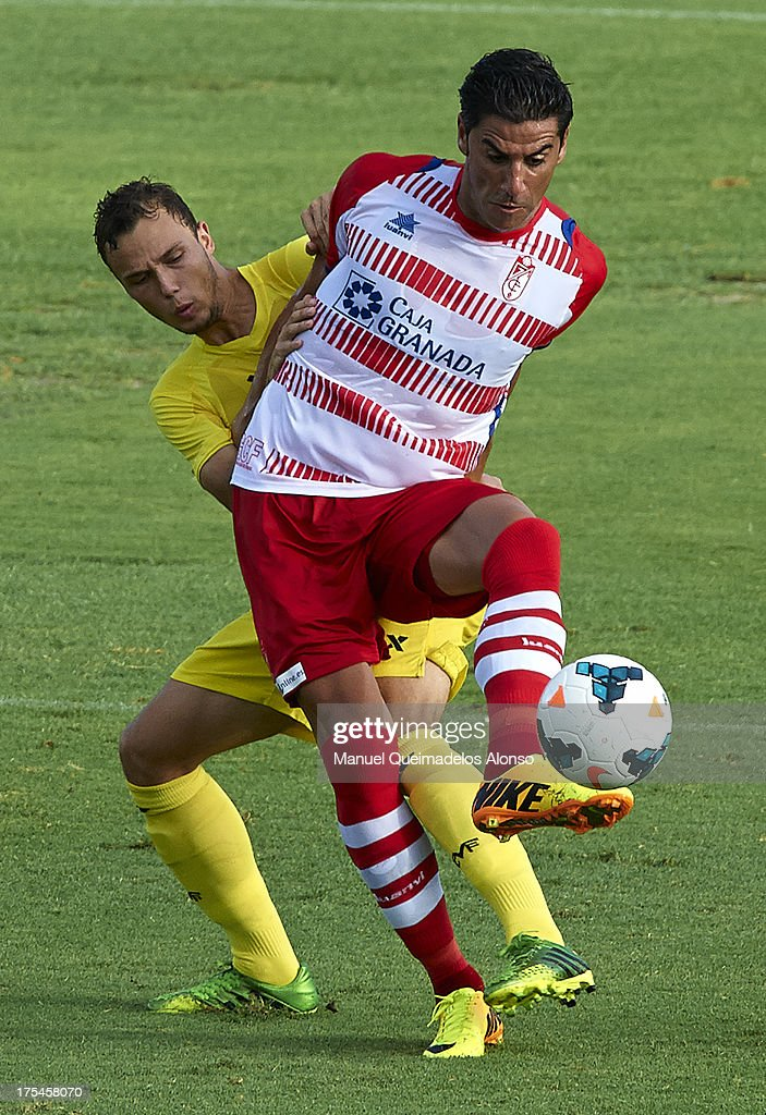 Riki (R) of Granada competes for the ball with Pablo Iniguez of Villarreal during a friendly match between Villarreal CF and Granada FC at La Manga Club on August 03, 2013 in La Manga, Spain.