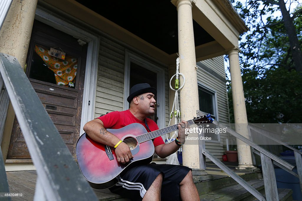 Riki Rocksteady plays guitar and sings as he sits on his front porch in Boston's Brighton neighborhood on August 22, 2014.