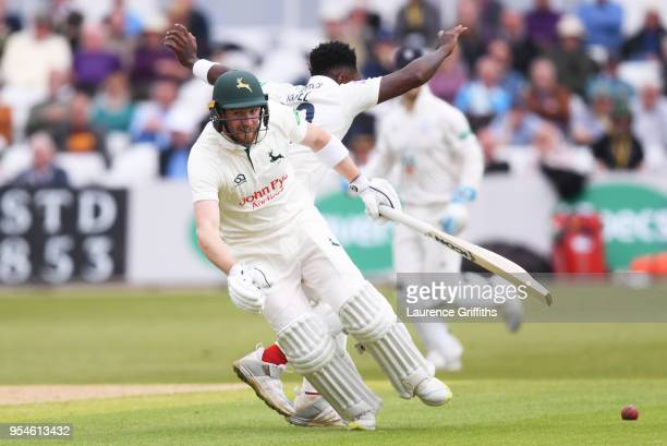 Riki Wessels of Nottinghamshire and Fidel Edwards of Hampshire collide during the Specsavers County Championship Division One match between...