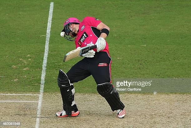 Riki Wessels of the Sydney Sixers reels backwards after the ball was lodged in his helmet by a delivery from Kane Richardson of the Strikers during...