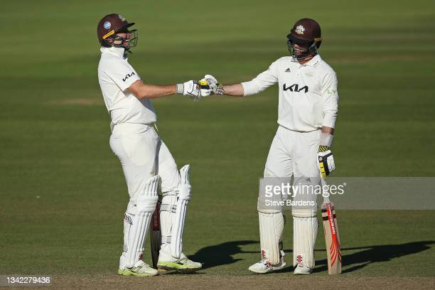 Rikki Clarke of Surrey fist bumps with Ben Foakes in his final appearance on day four during the LV= Insurance County Championship match between...