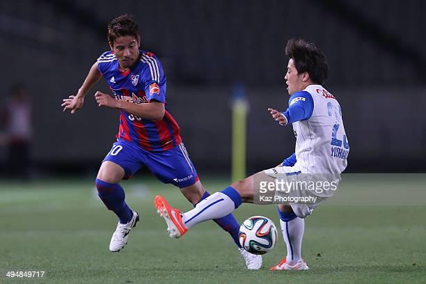 Riku Matsuda of FC Tokyo and Yoshiaki Takagi of Shimizu S-Pulse compete for the ball during the J.League Yamazaki Nabisco Cup Group A match between...