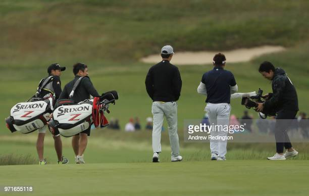 Rikuya Hoshino of Japan and Shota Akiyoshi of Japan walk with their caddies during practice rounds prior to the 2018 US Open at Shinnecock Hills Golf...