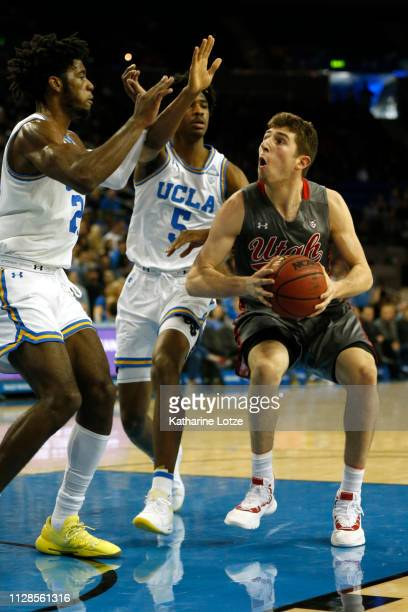 Riley Battin of the Utah Utes looks for an opening under the hoop as Jalen Hill of the UCLA Bruins and Chris Smith of the UCLA Bruins block during...