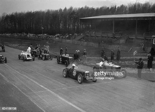 Riley Brooklands of H Hodgson and MG Magnette of H Levy Donington Park Leicestershire 1935 Artist Bill BrunellRight of centre Riley Brooklands 1089...
