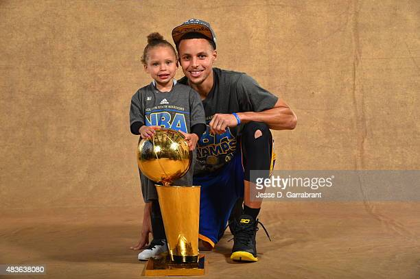 Riley Curry and Stephen Curry of the Golden State Warriors poses for a portrait with the Larry O'Brien trophy after defeating the Cleveland Cavaliers...