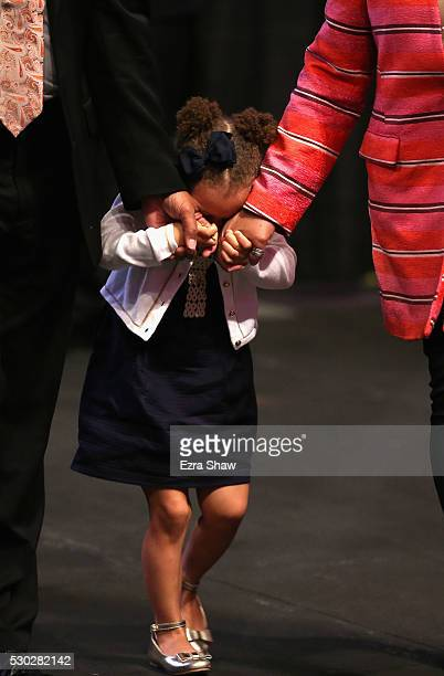 Riley Curry the daughter of Stephen Curry of the Golden State Warriors covers her face as she walks in to a press conference where it was announced...