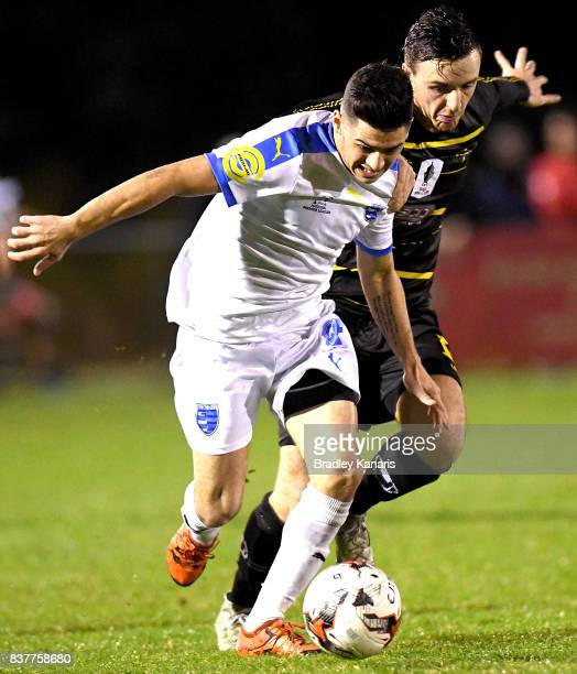 Riley Dillon Gold Coast City attempts to break away from the defence of Alex Janovsky of Moreton Bay during the FFA Cup round of 16 match between...