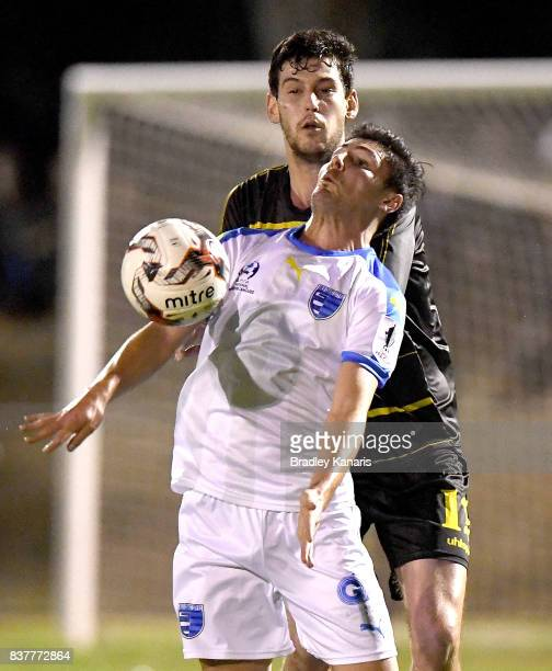 Riley Dillon of Gold Coast City is pressured by the defence of Corey Lucas of Moreton Bay during the FFA Cup round of 16 match between Moreton Bay...