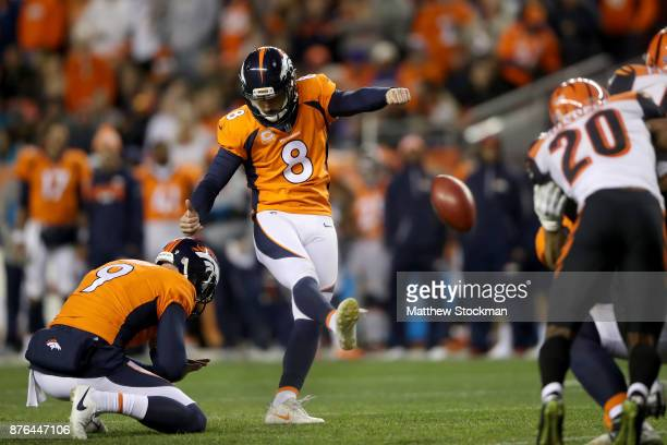 Riley Dixon holds as Brandon McManus of the Denver Broncos kicks an extra point against the Cincinnati Bengals at Sports Authority Field at Mile High...