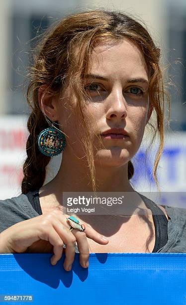 Riley Keough attends a rally, wearing an earring showing a photo of her grandparents and mother in support of a lawsuit against The Army Corps Of...