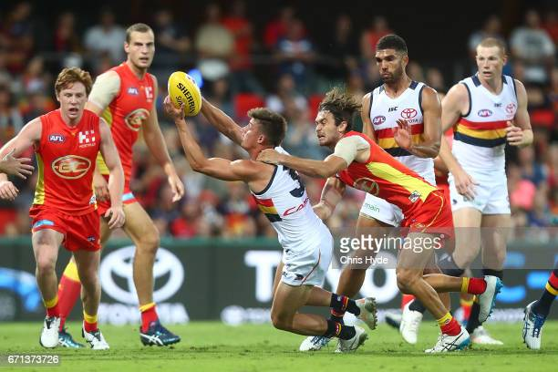 Riley Knight of the Crows is tackled by Jarrod Harbrow of the Suns during the round five AFL match between the Gold Coast Suns and the Adelaide Crows...