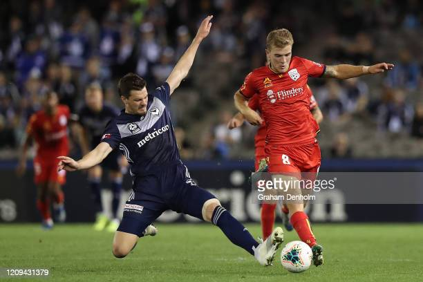 Riley McGree of Adelaide United is challenged during the round 21 A-League match between the Melbourne Victory and Adelaide United at Marvel Stadium...