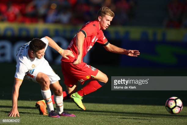 Riley McGree of Adelaide United is tackled by Brandon Borrello of Brisbane Roar during the round 23 ALeague match between Adelaide United and the...