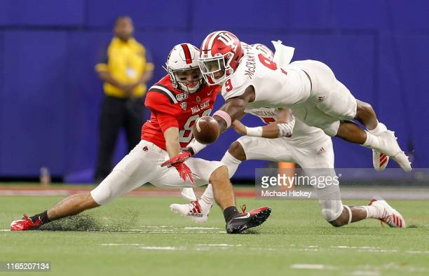 Riley Miller of the Ball State Cardinals reaches for the ball as Marcelino Ball of the Indiana Hoosiers breaks up the receptions during the first...