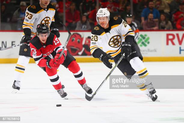 Riley Nash of the Boston Bruins and Nico Hischier of the New Jersey Devils pursue a loose puck during the game at Prudential Center on November 22...