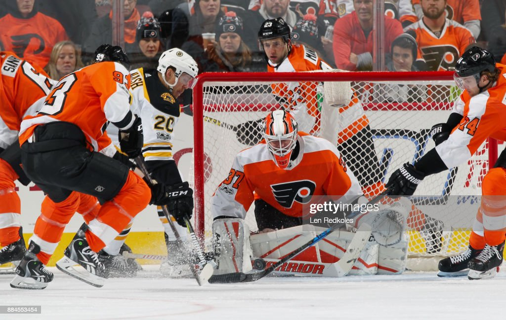 Riley Nash #20 of the Boston Bruins battles for the loose puck in front of Brian Elliott #37 of the Philadelphia Flyers with Jakub Voracek #93 and Sean Couturier #14 on December 2, 2017 at the Wells Fargo Center in Philadelphia, Pennsylvania. The Bruins went on to defeat the Flyers 3-0.