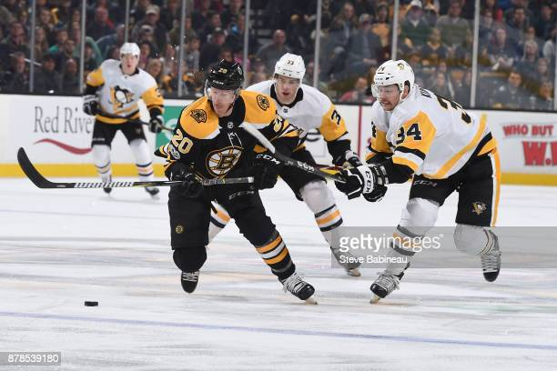 Riley Nash of the Boston Bruins skates after the puck against Greg McKegg and Tom Kuhnhackl of the Pittsburgh Penguins at the TD Garden on November...
