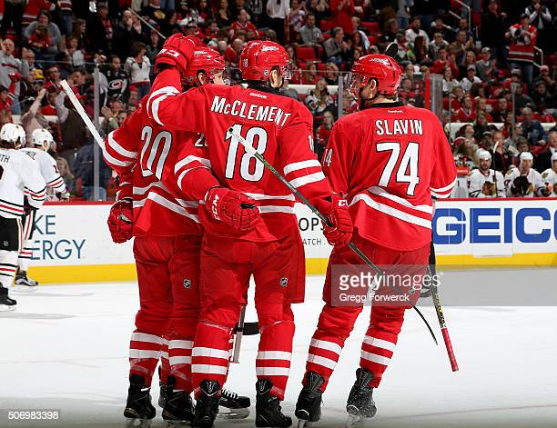 Riley Nash of the Carolina Hurricanes celebrates with teammates Jay McClement and Jaccob Slavin after scoring a first period goal during an NHL game...