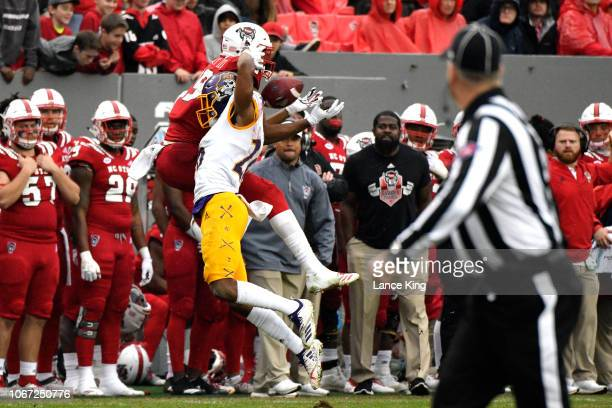 J Riley of the North Carolina State Wolfpack makes a catch against Colby Gore of the East Carolina Pirates at CarterFinley Stadium in the third...