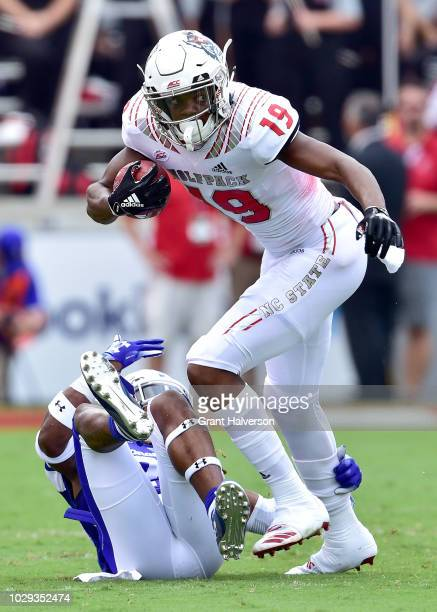 J Riley of the North Carolina State Wolfpack runs through Quavian White of the Georgia State Panthers during their game at CarterFinley Stadium on...