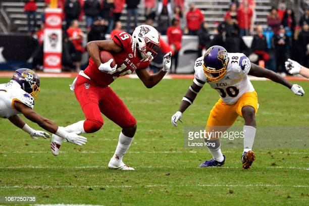 J Riley of the North Carolina State Wolfpack runs with the ball against Colby Gore and Bruce Bivens of the East Carolina Pirates in the third quarter...