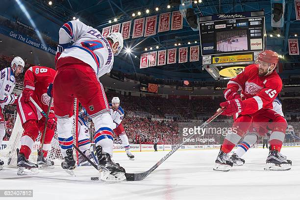 Riley Sheahan and Justin Abdelkader of the Detroit Red Wings battle for the puck behind the net with Adam Clendening of the New York Rangers during...